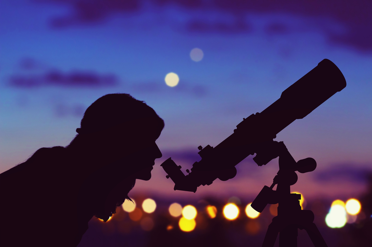 Girl looking at the stars with telescope beside her and de-focused city lights. free summer events